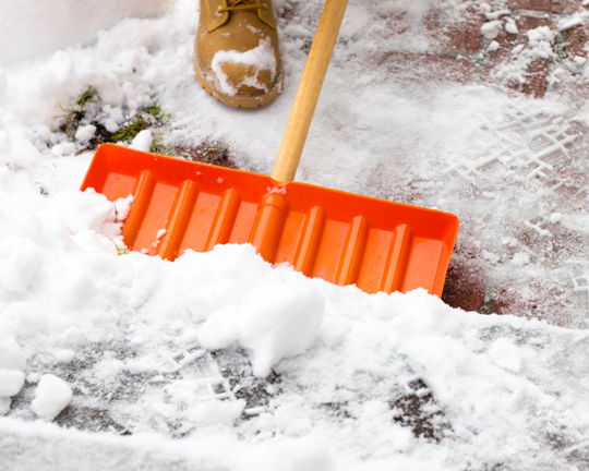 person shoveling snow with orange shovel